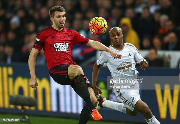 Gareth McAuley of West Bromwich Albion clears the ball under pressure from Andre Ayew of Swansea City during the Barclays Premier League match...