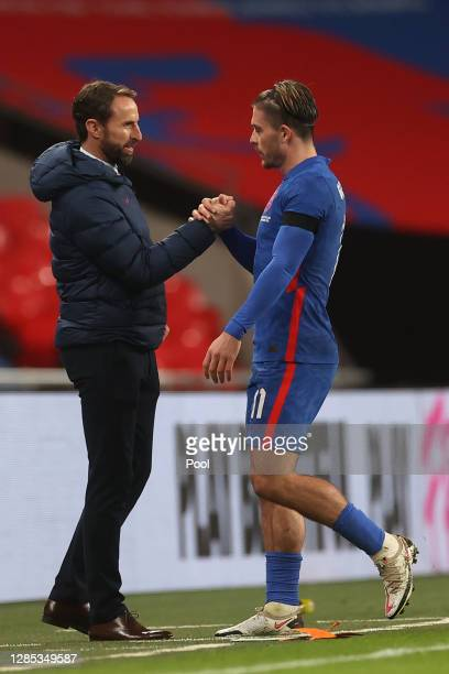 Gareth Southgate, Head Coach of England shakes hands with Jack Grealish of England as he is substituted during the international friendly match...