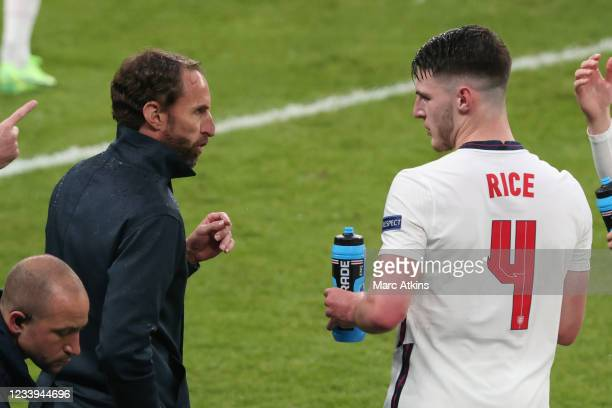 Gareth Southgate, Head Coach of England speaks with Declan Rice during the UEFA Euro 2020 Championship Final between Italy and England at Wembley...