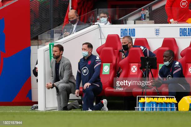 Gareth Southgate, Head Coach of England, Steve Holland, Assistant Coach of England and Chris Powell, Coach of England take a knee in support of the...