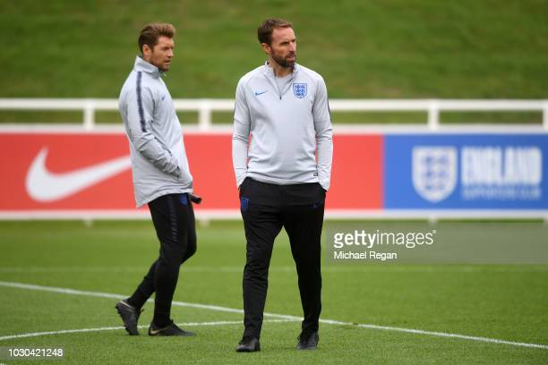 Gareth Southgate Manager of England and Allan Russell England Striker Coach speak during a training session at St Georges Park on September 10 2018...