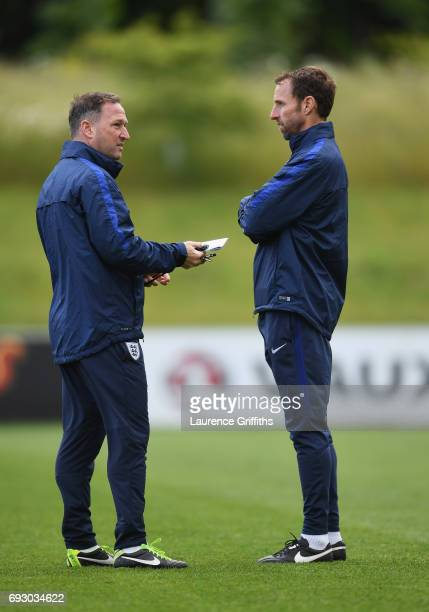 Gareth Southgate manager of England and assistant manager Steve Holland in discussion during a training session as part of England media access at St...