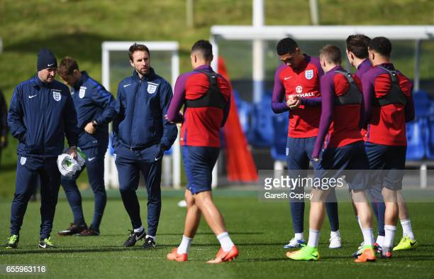Gareth Southgate manager of England and assistant Steve Holland talk to players during an England training session at St Georges Park on March 21...