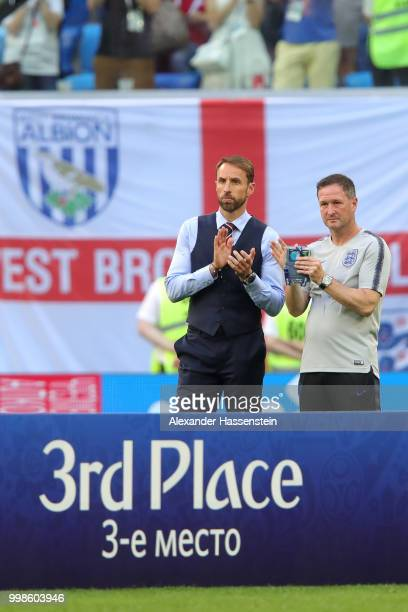 Gareth Southgate Manager of England and England assistant manager Steve Holland applaud Belgium as they recieve their third place medal after the...