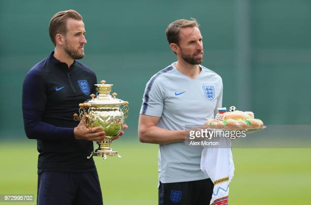 Gareth Southgate Manager of England and Harry Kane of England a presented with gifts during a training session as part of the England media access at...