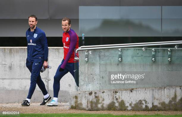 Gareth Southgate manager of England and Harry Kane of England walk to the pitch during an England training session on the eve of their FIFA World Cup...