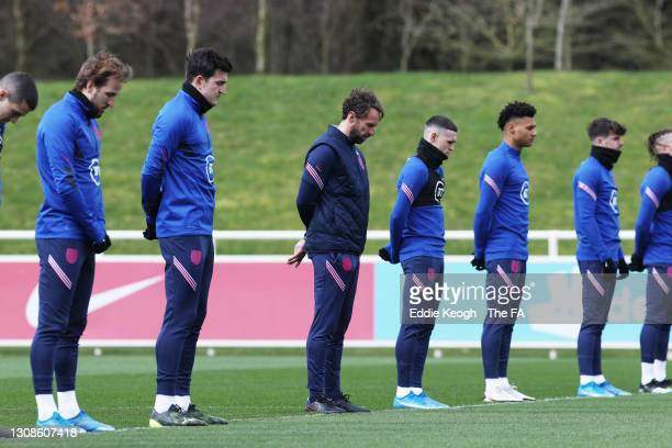 Gareth Southgate, Manager of England stands with his players as they observe a minutes silence for victims of the COVID-19 Pandemic during a training...
