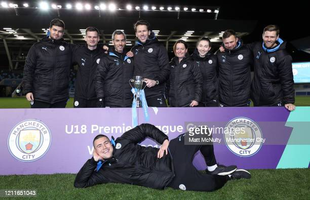 Gareth Taylor Manager of Manchester City and his coaching staff pose with the trophy after the Under 18's Premier League 2 Cup Final at The Academy...