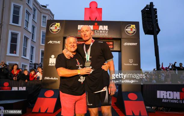 Gareth Thomas celebrates with his partner on completing his first Ironman on September 15, 2019 in Tenby, Wales.