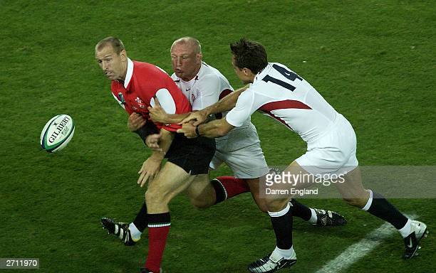 Gareth Thomas of Wales gets the ball away from the tackle of Neil Back and Dan Luger of England during the Rugby World Cup Quarter Final match...