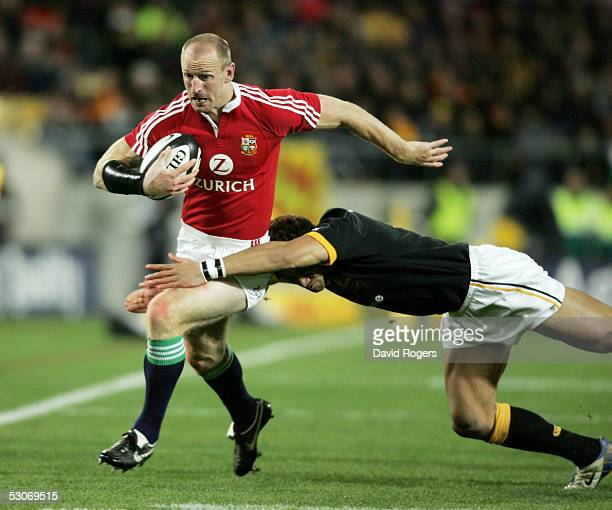 Gareth Thomas the Lions wing is tackled by Roy Kinikinilau during the match between the British and Irish Lions and Wellington at The Westpac Stadium...