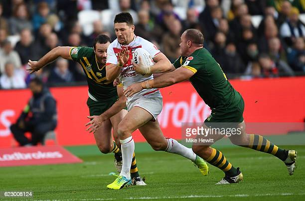Gareth Widdop of England is tackled by Josh Duggan and Matthew Scott of Australia during the Four Nations match between the England and Australian...