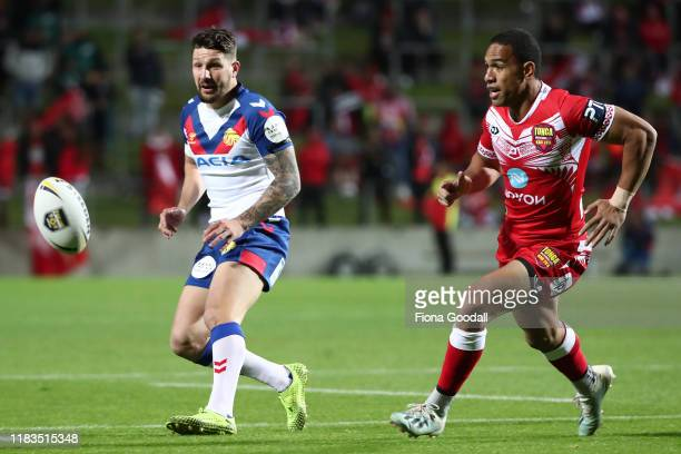 Gareth Widdop of Great Britain kicks the ball through defended by William Hopoate of Tonga during the International Rugby League Test match between...
