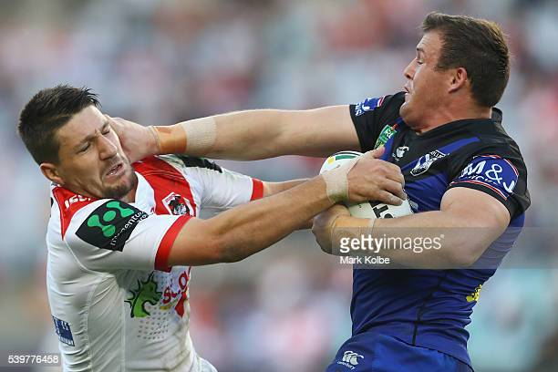 Gareth Widdop of the Dragons is fends away by Josh Morris of the Bulldogs during the round 14 NRL match between the St George Illawarra Dragons and...