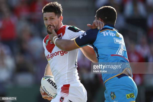 Gareth Widdop of the Dragons is tackled by Ashley Taylor of the Titans during the round 23 NRL match between the St George Illawarra Dragons and the...