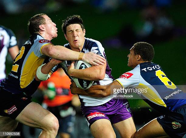 Gareth Widdop of the Storm is tackled by Glenn Hall and Ray Thompson of the Cowboys during the round three NRL match between the North Queensland...