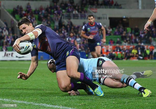 Gareth Widdop of the Storm scores a try despite the tackle of Todd Carney of the Sharks during the round 13 NRL match between the Melbourne Storm and...