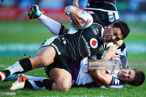 Gareth Widdop of the Storm tackles Elijah Taylor of the Warriors during the round 16 NRL match between the Warriors and the Melbourne Storm at Mt...