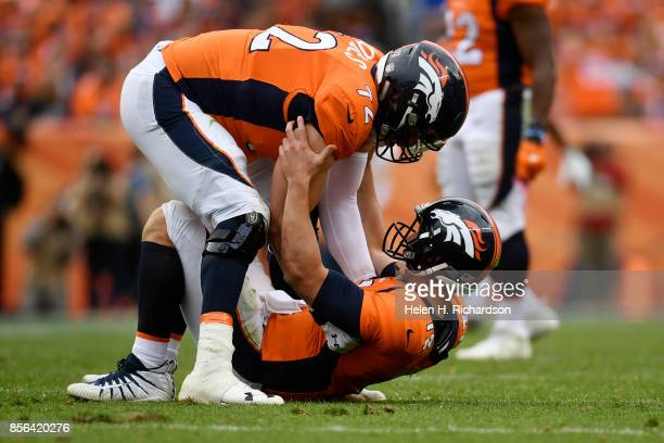 Garett Bolles of the Denver Broncos helps up Trevor Siemian against the Oakland Raiders during the fourth quarter on Sunday October 1 2017 The Denver...