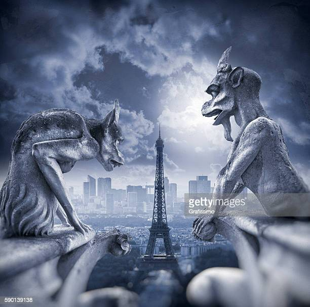 Gargoyle figur on Notre Dame with Eiffel Tower at night