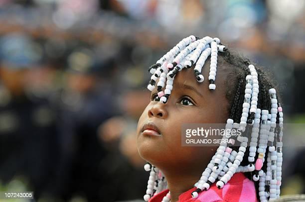 A Garifuna ethnic group girl observes as some 15000 National Police agents start the Navidad Feliz operation in tegucigalpa on December 1 2010...