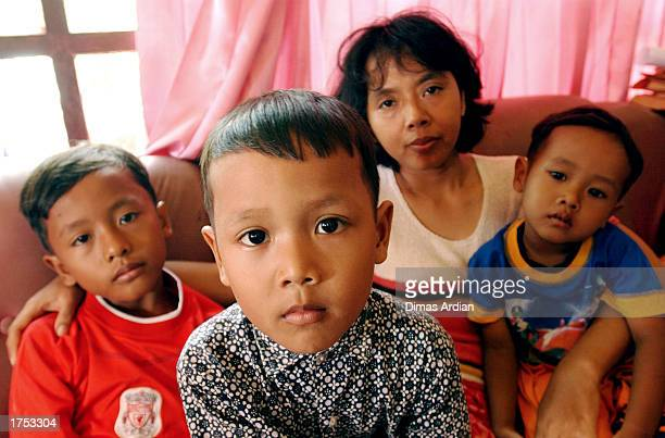 Garil Arnanda Dwiga Meza Endang Isnaini and Izul Haq pose in their living room of their home January 30 2003 in Denpasar Bali Indonesia Endang is...