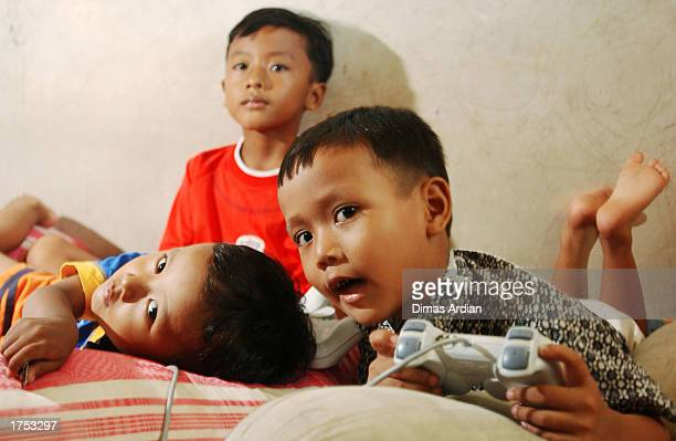 Garil Arnanda Izul Haq and Dwiga Meza play a game on Playstation January 30 2003 in Denpasar Bali Indonesia Their father Aris Munandar was killed in...