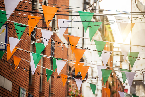 Garland with irish flag colors in a street of Dublin, Ireland - Saint Patrick day celebration concept 837185812