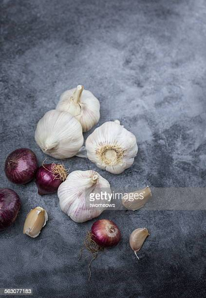Garlic and shallots on rustic kitchen counter top.