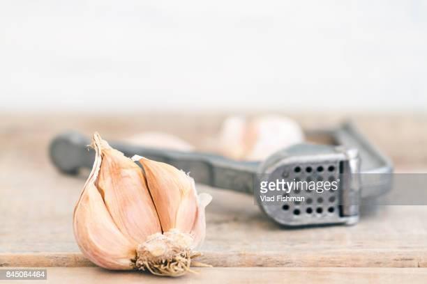 garlic cloves with vintage metal garlic press or crusher on a wood rustic table background - cabeza de ajos fotografías e imágenes de stock