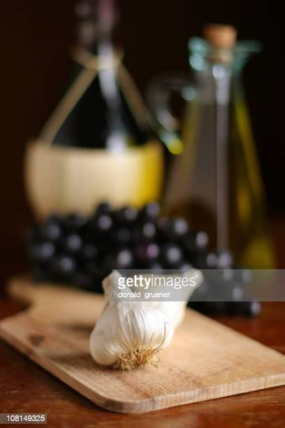 uvas y ajo, aceite de oliva sobre tabla de cortar - cabeza de ajos fotografías e imágenes de stock