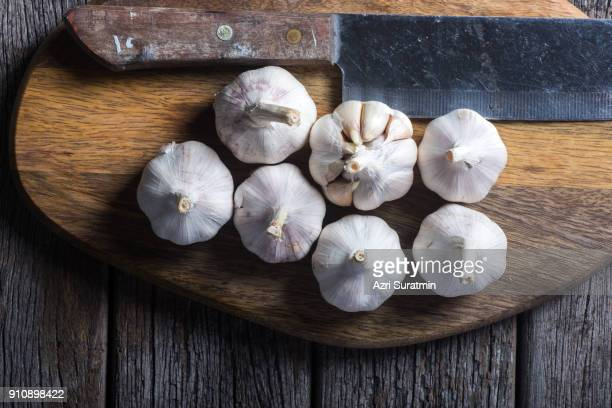 garlic on wooden chopping board. - garlic stock pictures, royalty-free photos & images