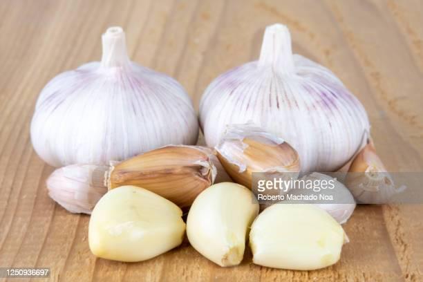garlic over a wooden surface, studio shot - cabeza de ajos fotografías e imágenes de stock