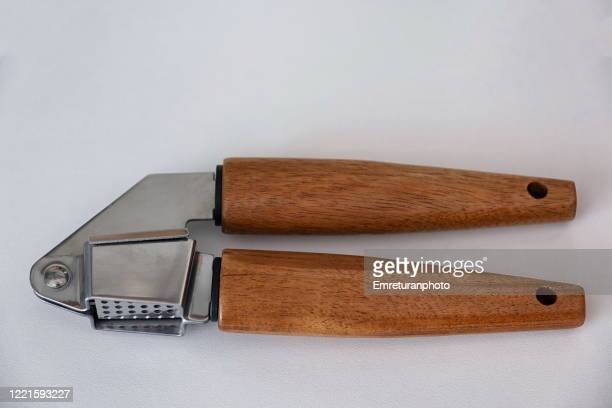 garlic press with wooden handle on a white surface. - emreturanphoto stock pictures, royalty-free photos & images