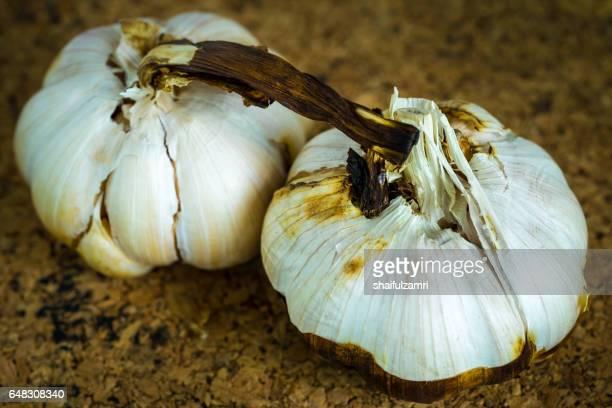 garlic roast over cork sheet - shaifulzamri stockfoto's en -beelden