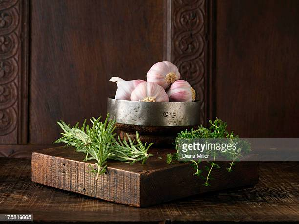 Garlic, rosemary and thyme on rustic wooden board