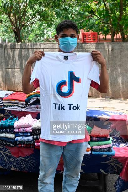 Garment street vendor poses for a picture in front of his stall with a t-shirt with the logo of the social media video-sharing application Tik Tok in...