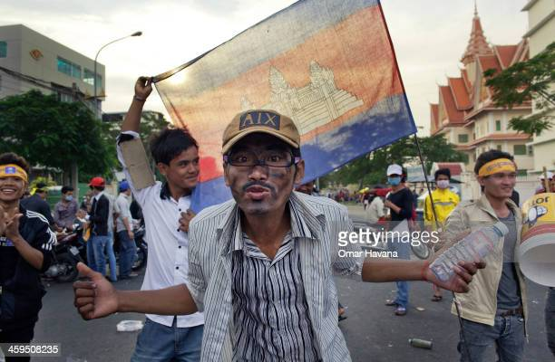 A garment worker shouts in protest of the new minimum wage approved by the Cambodian Government during a strike in front of the Ministry of Labour on...