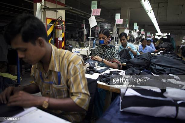 Garment workers assemble pairs of Arnold Palmer pants inside the Interlink Garments factory on November 25 2009 in Gazipur Bangladesh Workers in the...