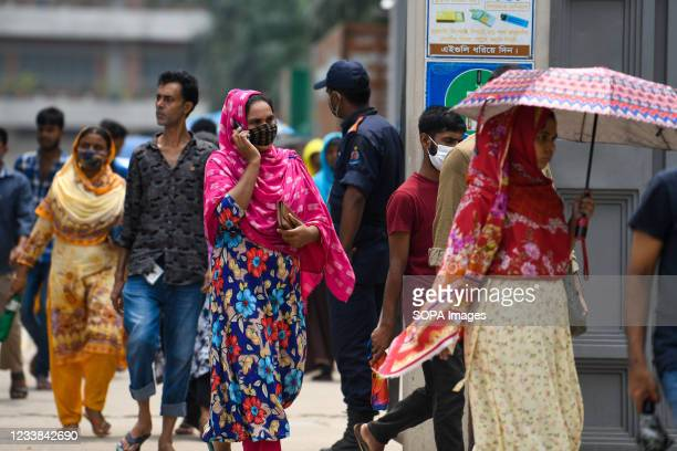 Garment workers come out of a factory during the lunch break as factories remain open despite a countrywide lockdown in Dhaka. Bangladesh enacted a...