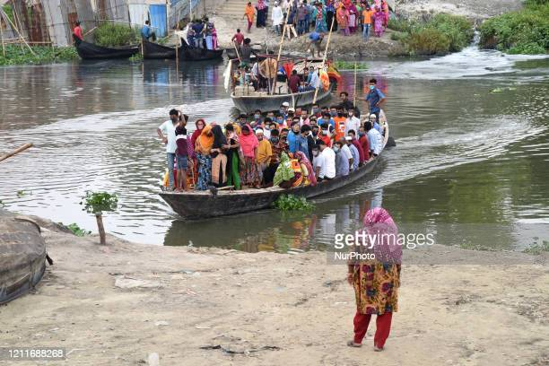 Garment workers wear face masks as they crossing river by boat during government imposed lockdown as a preventative measure against the COVID19...