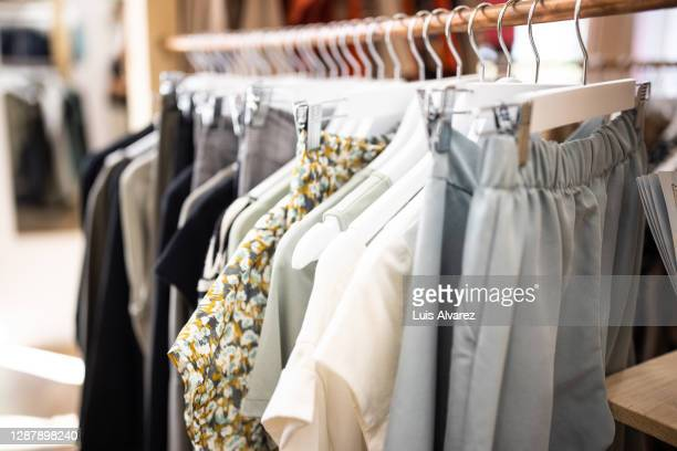 garments hanging on racks in fashion store - womenswear stock pictures, royalty-free photos & images