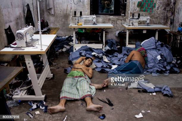 SADARGHAT DHAKA BANGLADESH Garments labourers sleep over the denim jeans in a local denim garments shop in Dhaka