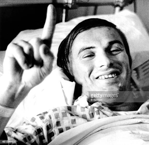 Garnet 'Ace' Bailey of the Boston Bruins signifies the Bruins are in 1st place as he lies in his hospital bed at Massachusetts General Hospital after...