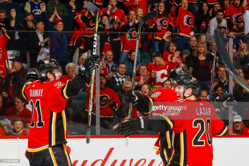 Garnet Hathaway #21, Curtis Lazar #20 and Matt Stajan #18 of the Calgary Flames celebrate in an NHL game on February 1, 2018 at the Scotiabank Saddledome in Calgary, Alberta, Canada.