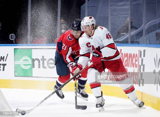 Garnet Hathaway of the Washington Capitals and Sami Vatanen of the Carolina Hurricanes play during the third period of the exhibition game prior to...