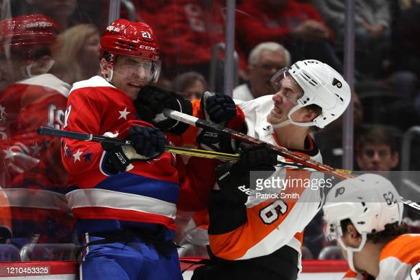 Garnet Hathaway of the Washington Capitals is checked by Travis Sanheim of the Philadelphia Flyers during the second period at Capital One Arena on...