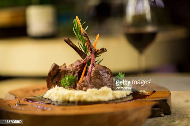garnished lamb chop on wooden serving plate - accompagnement photos et images de collection