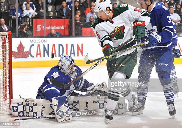 Garret Sparks of the Toronto Maple Leafs defends the goal as teammate Kasperi Kapanen battles with David Jones of the Minnesota Wild during NHL game...