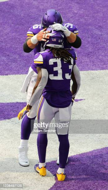Garrett Bradbury and Dalvin Cook of the Minnesota Vikings celebrate Cook's touchdown against the Green Bay Packers in the first quarter at US Bank...